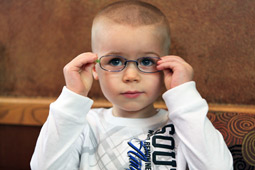 young boy trying on glasses