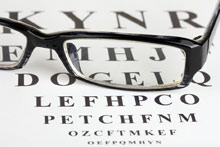 pair of eye glasses on eye test chart