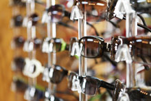 pairs of sunglasses on display wall in optical shop